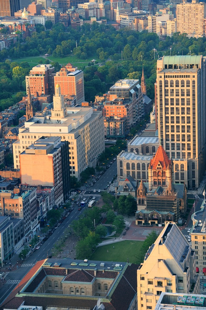 Boston city downtown aerial view with urban historical buildings at sunset.