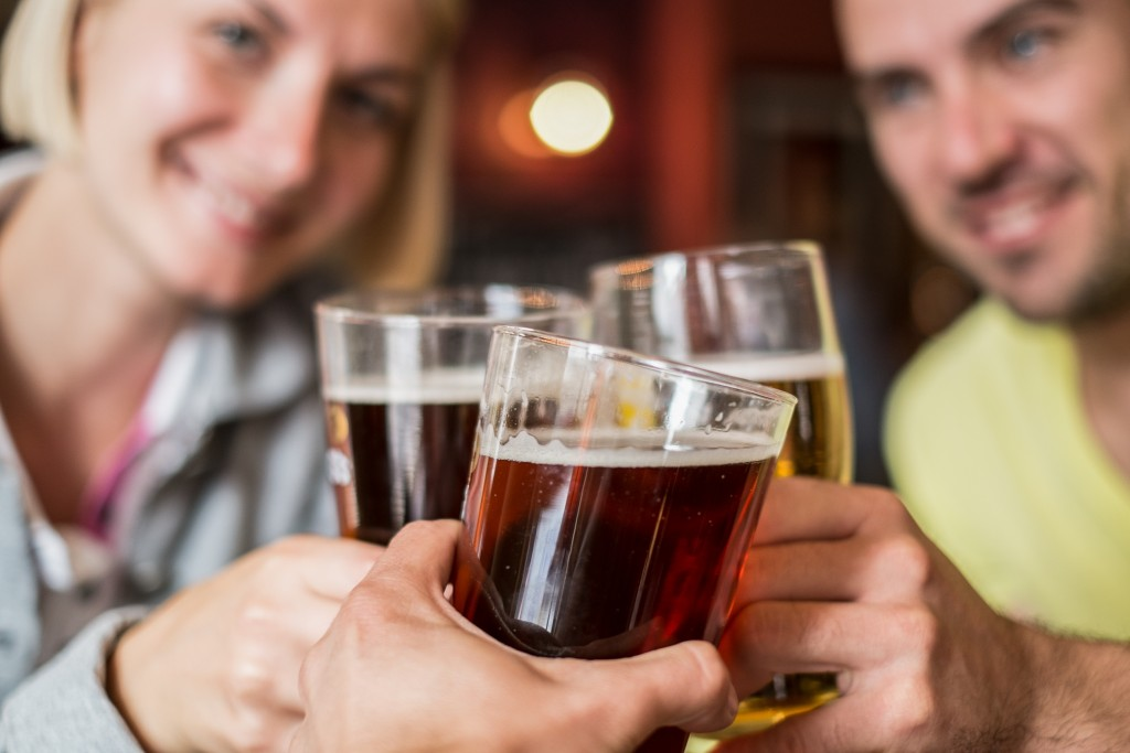 Friends with beer toasting in a pub